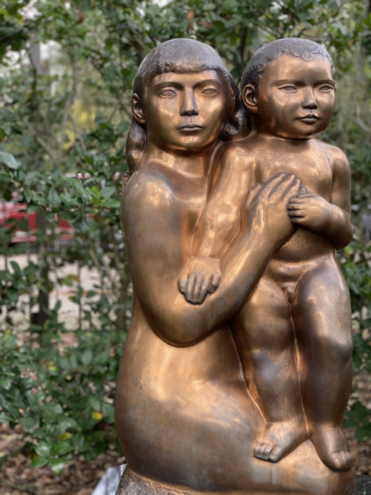 A bronze woman holding a child standing on her lap
