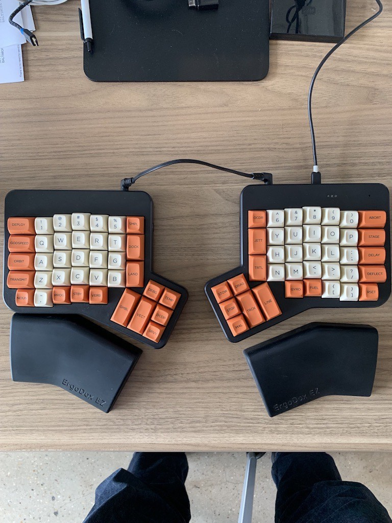 An Ergodox EZ keyboard in black with Godspeed MiTO keycaps in orange and cream.