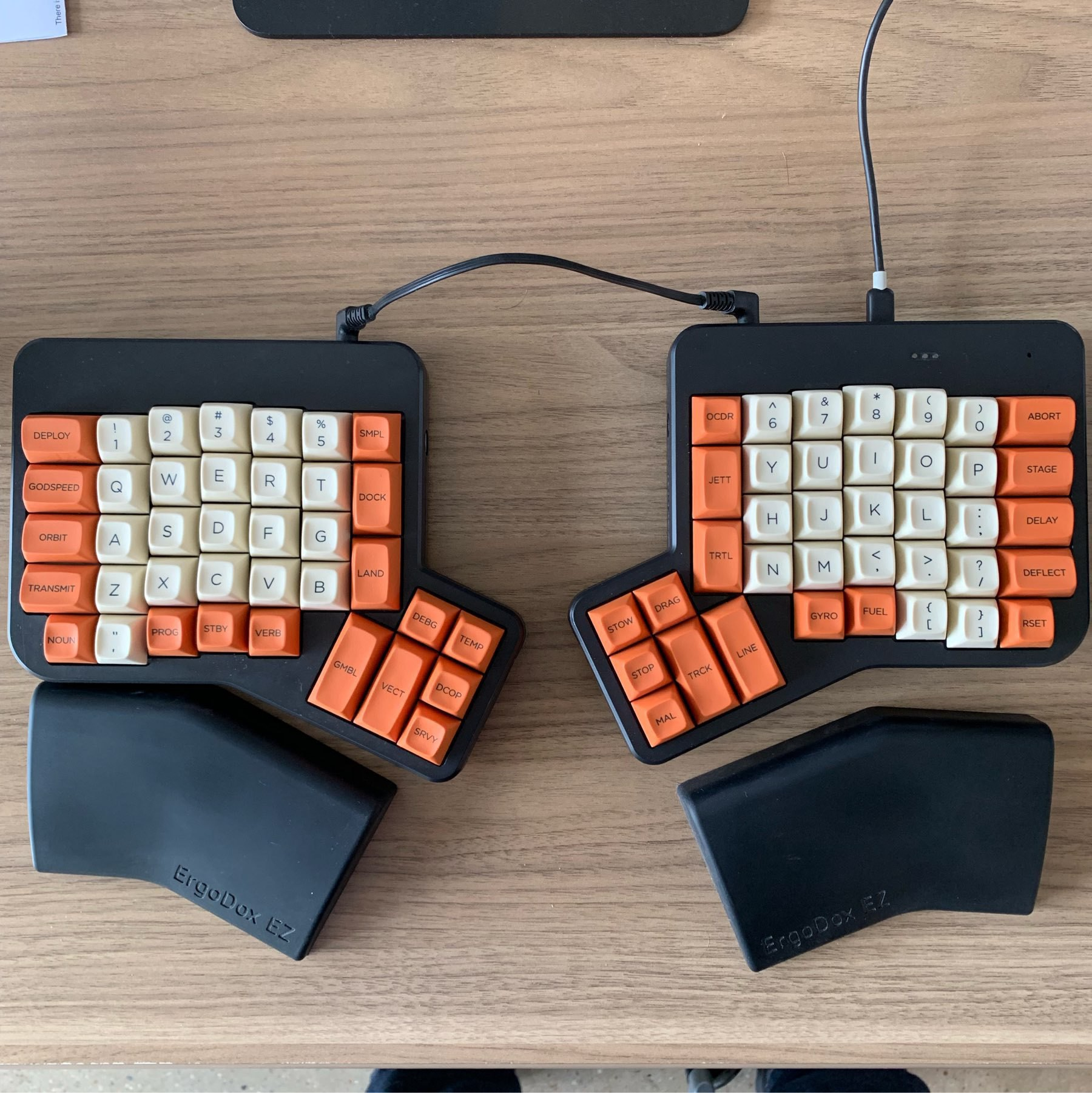 An ergodox keyboard with MiTo Godspeed keycaps in orange and white.