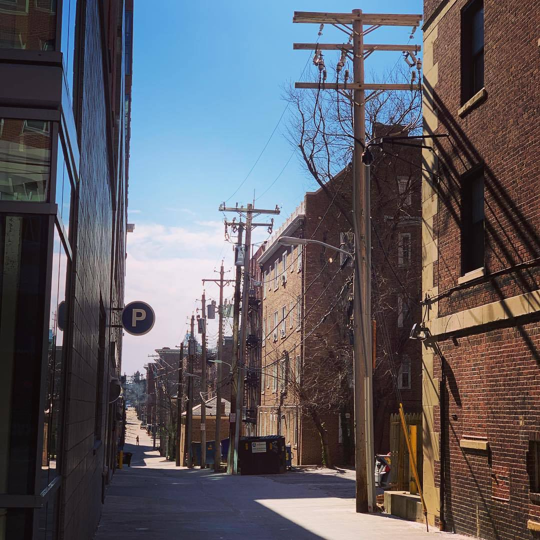 "Baltimore alleyway with electric poles and dumpsters behind an ""A"" street"