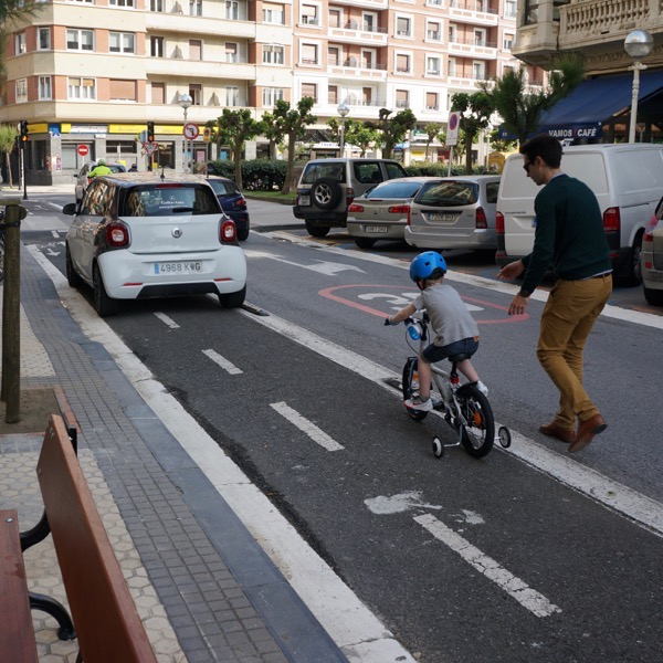 A child with training wheels riding his bike in a dedicated bike lane with his father at his side, while a small white car blocks the bike lane.