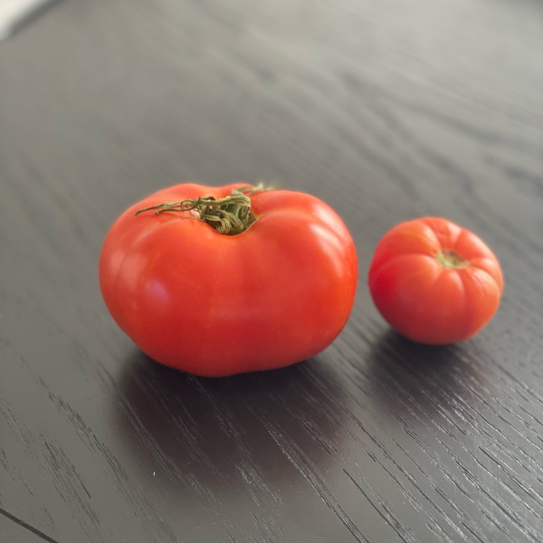 Two ripe tomatoes on a black table.