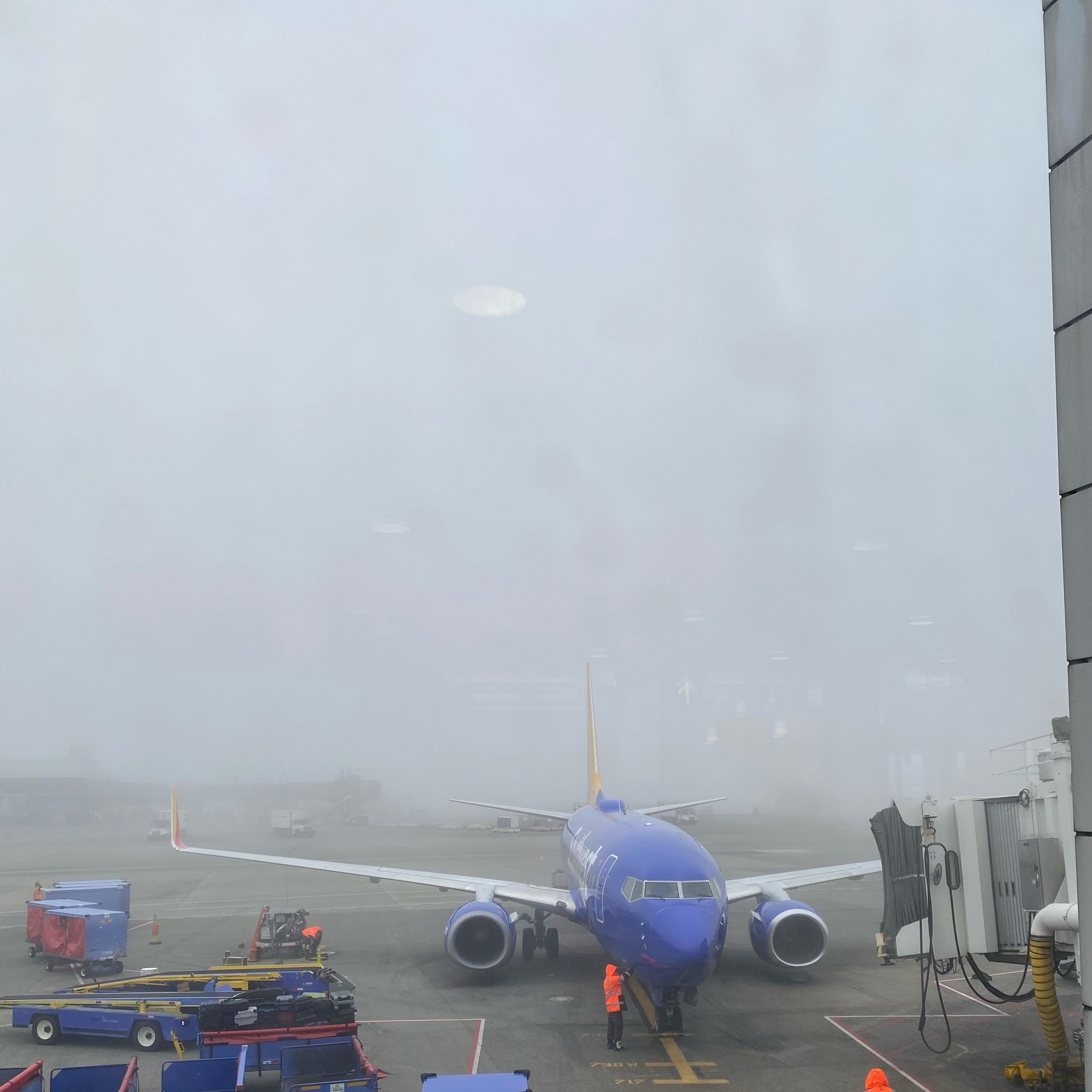 A Southwest Airlines 737 pulls up to the gate under heavy fog that obscures the view past 200 or so feet.
