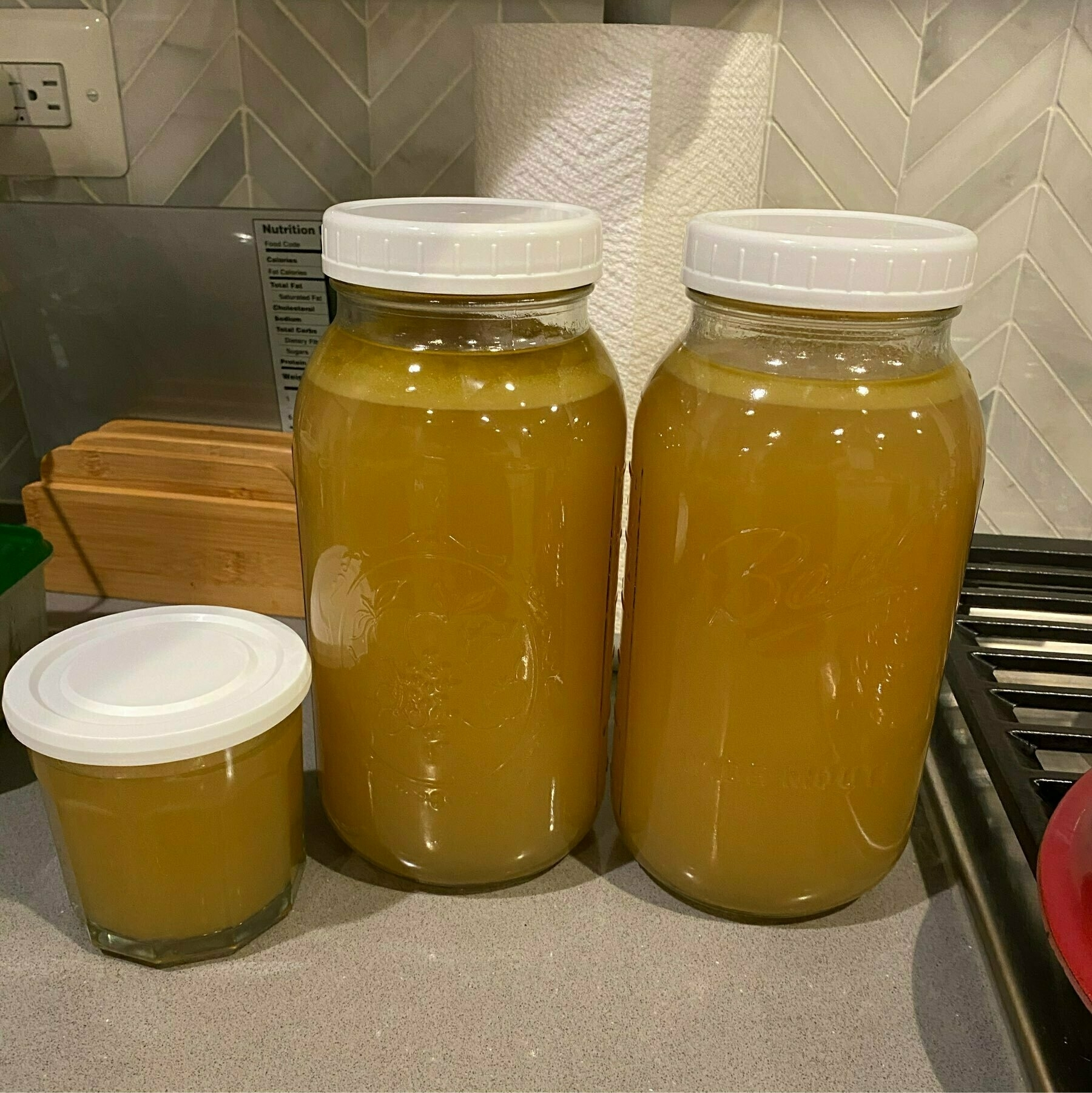 Two large mason jars of turkey stock and a small cup
