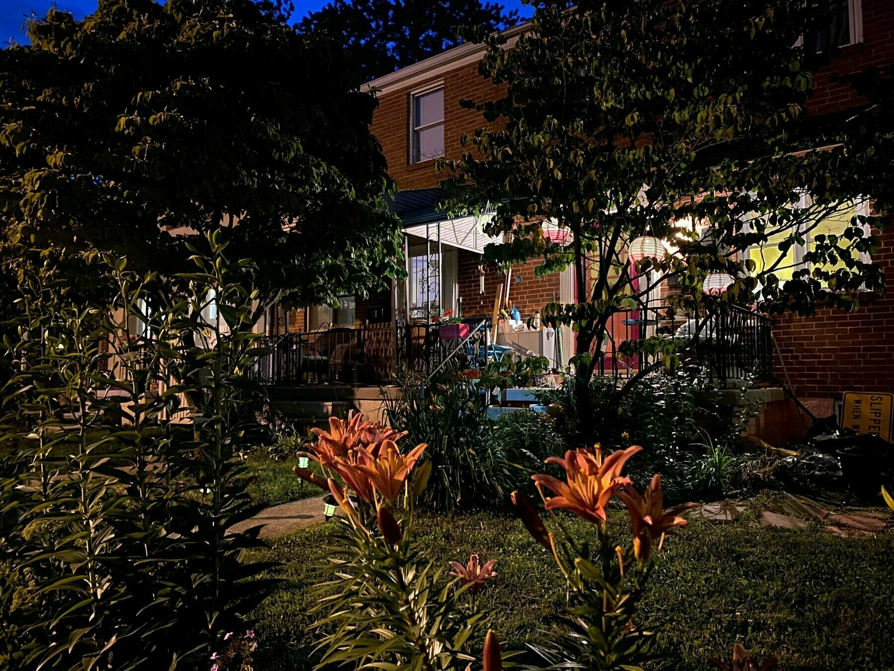 A nighttime photo of a house with latterns in its tree, a porch, and great flowers.