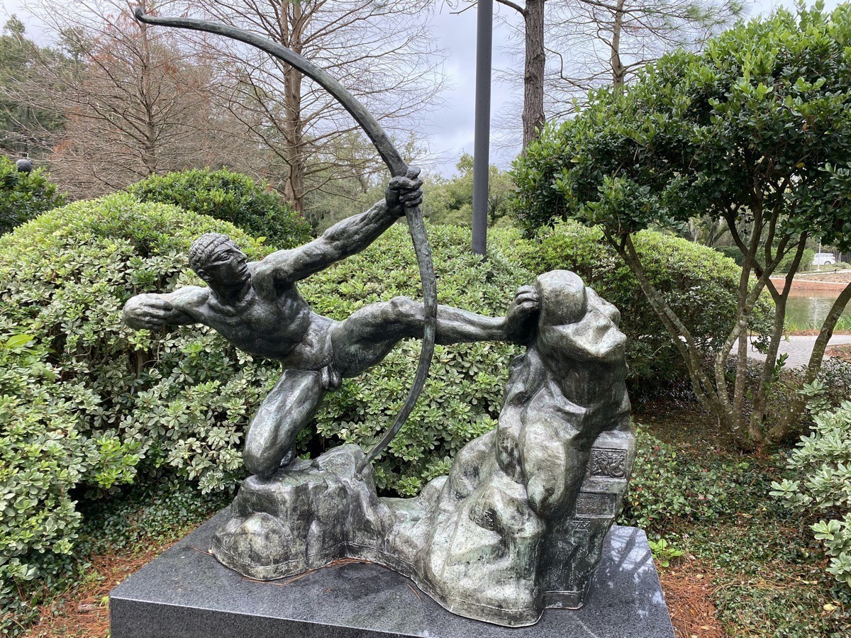 A statue Hercules leaning back holding an arrow