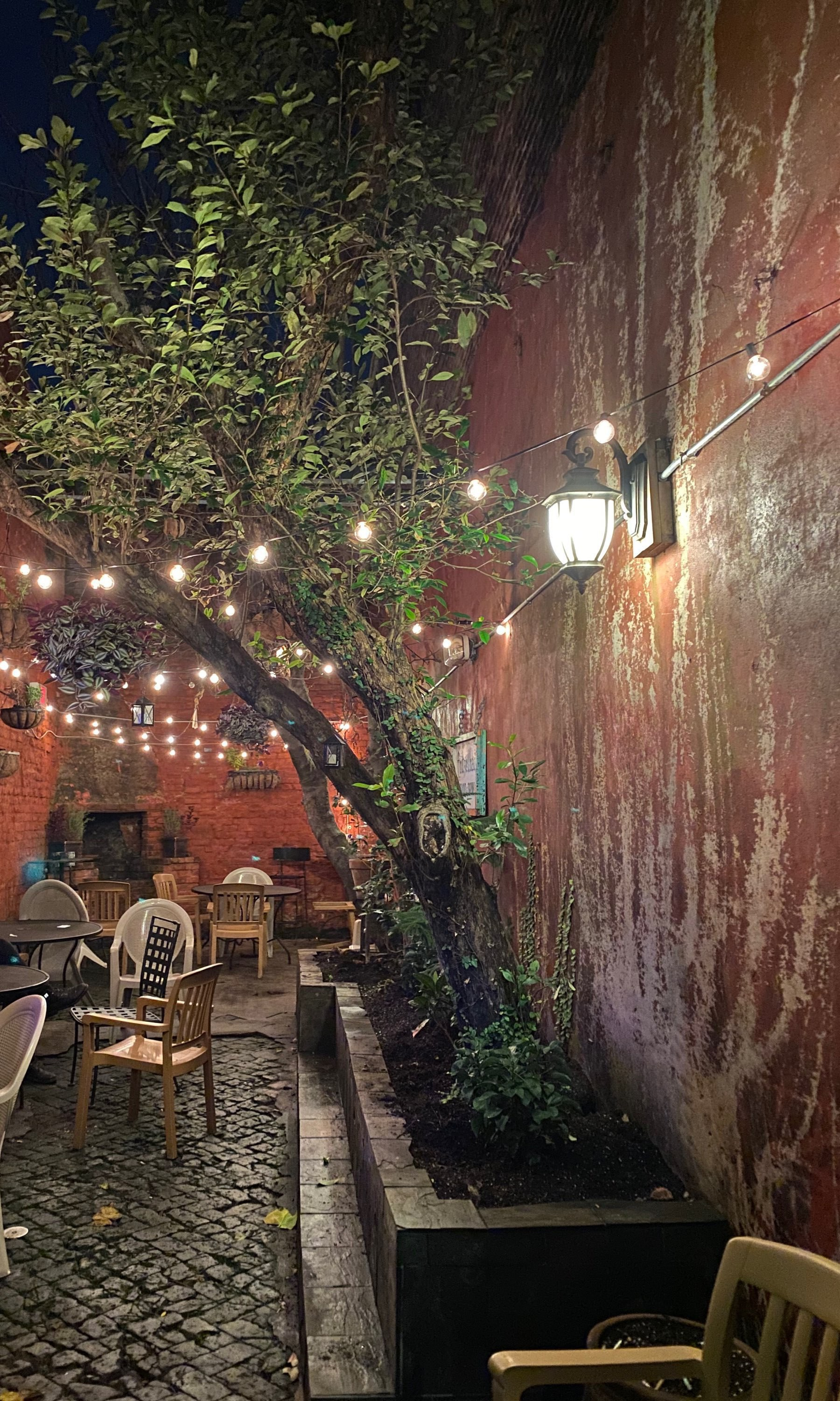 A courtyard with stone floors, brick walls, a tree, and chairs at night under strung up lights