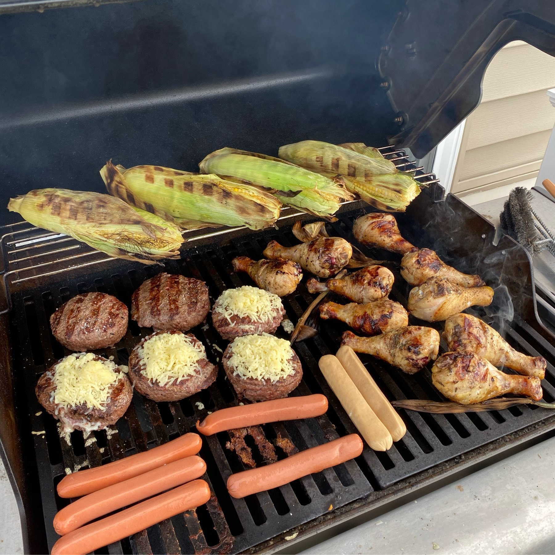 A grill with corn, burgers, hot dogs, and chicken legs.