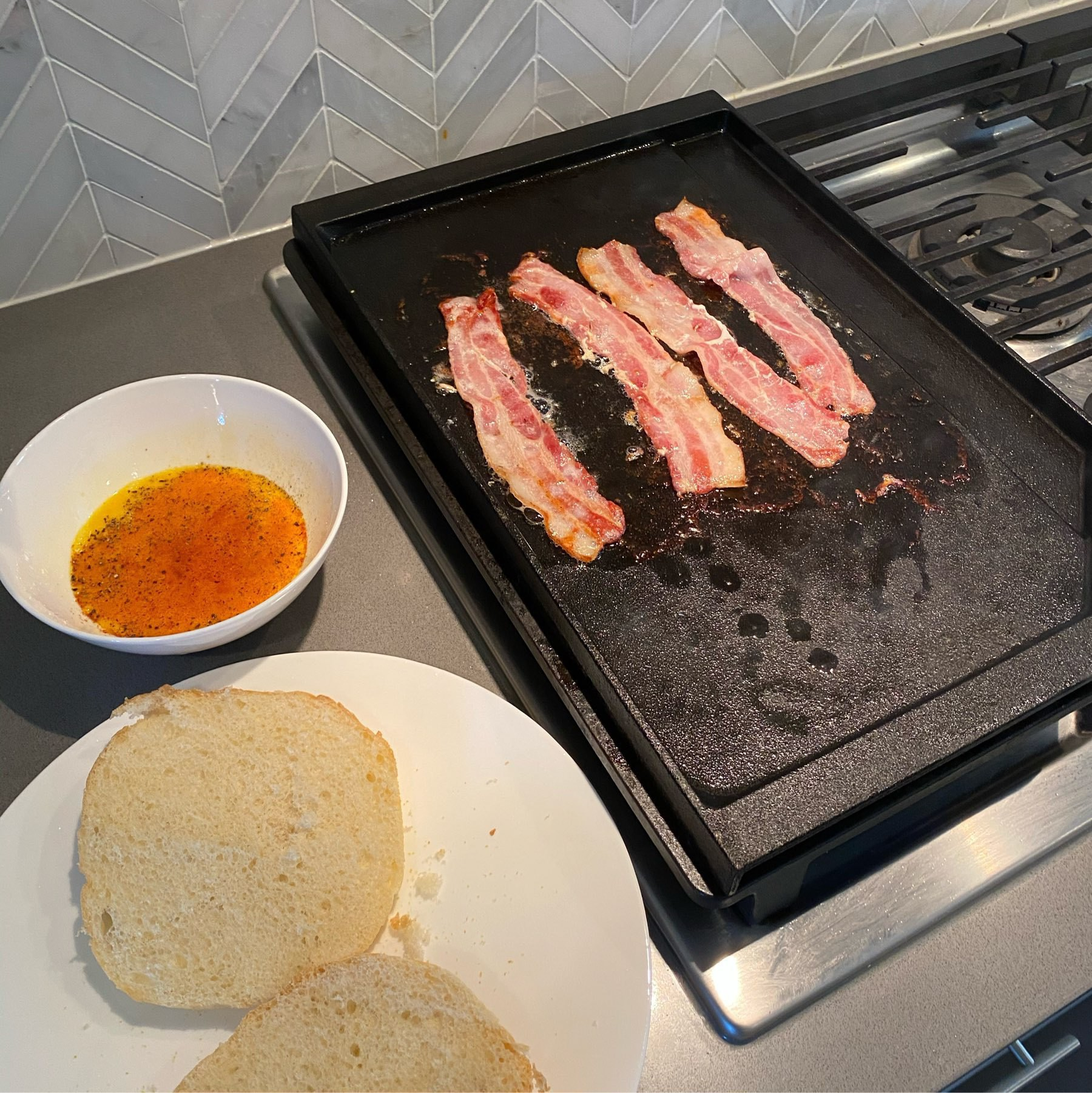 Bacon on a gas range griddle.