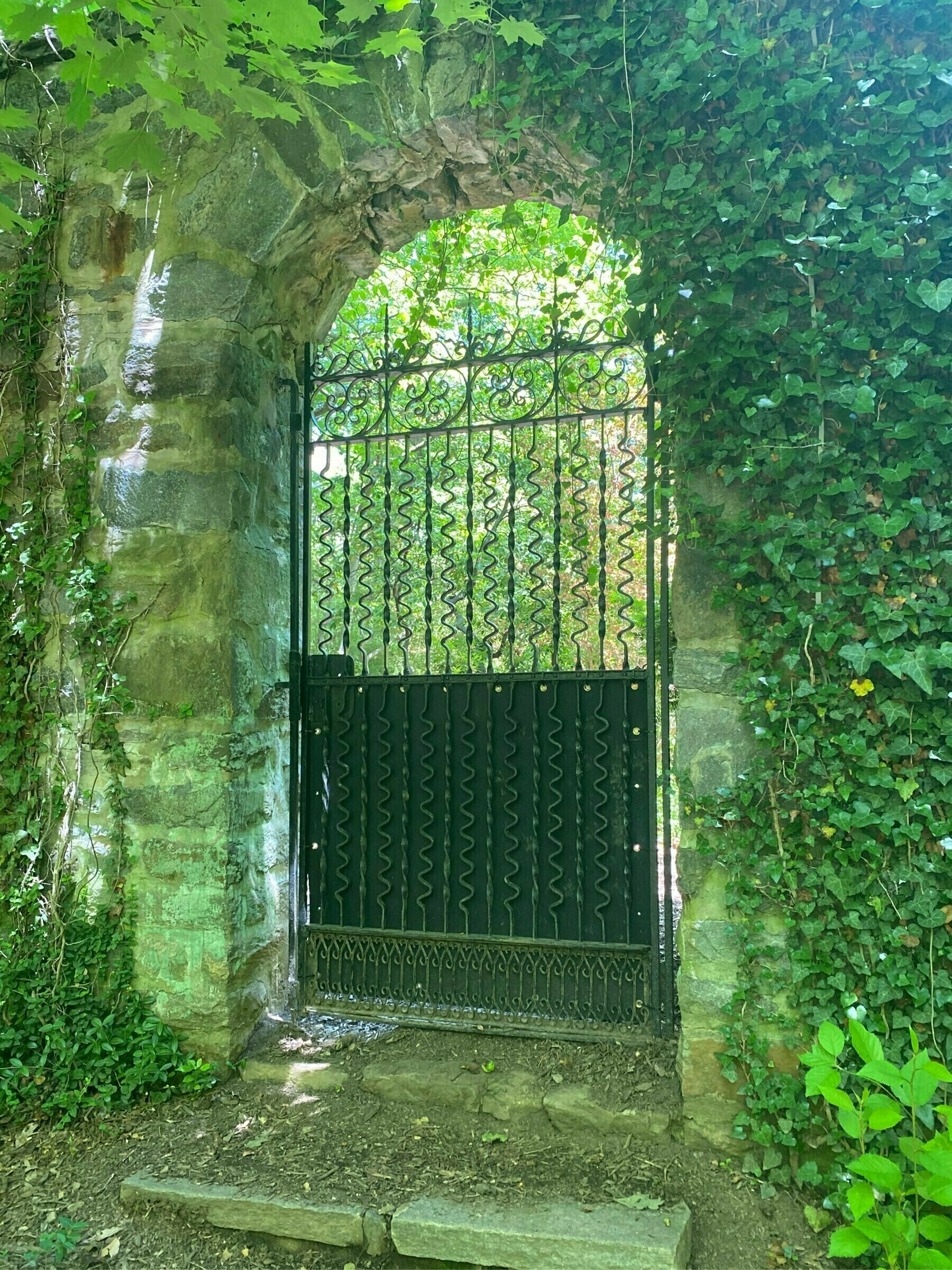 A stone archway with an iron gate surrounded by greenery