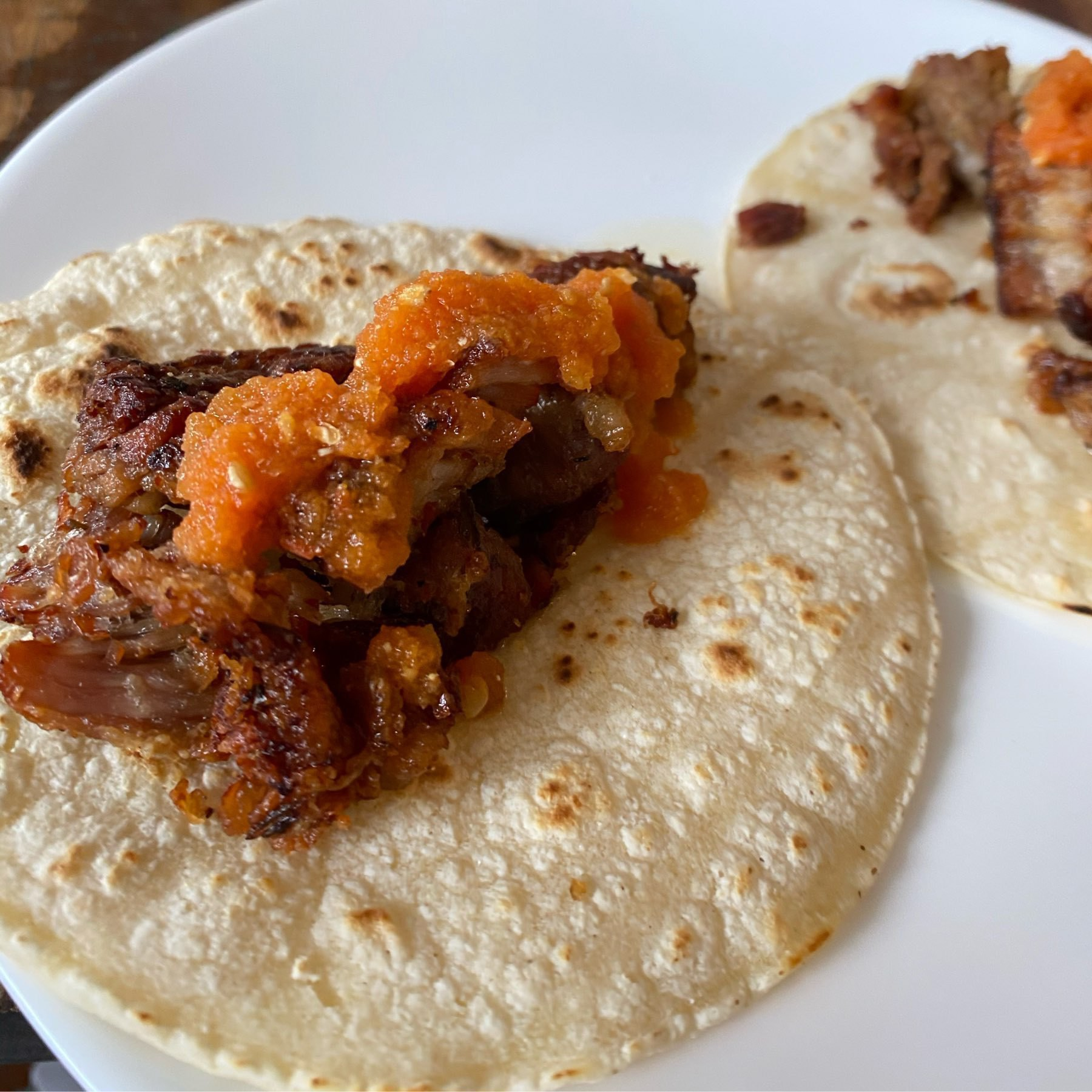 Carnitas on tortillas with red salsa