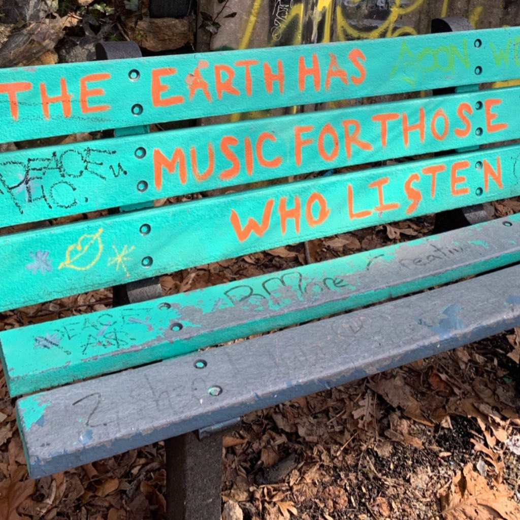 """A blue bench with the phrase """"The Earth has Music for those who Listen"""" painted in orange on the back."""