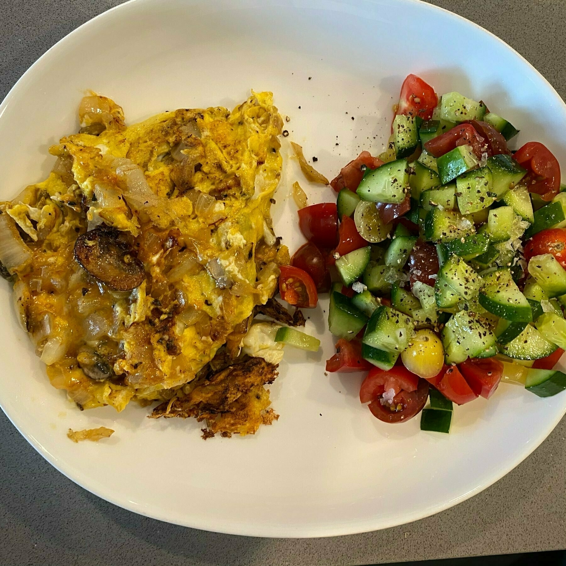 Left, egg cheese, mushroom, and onion scramble. Right, well-seasoned cucumber and tomato salad.