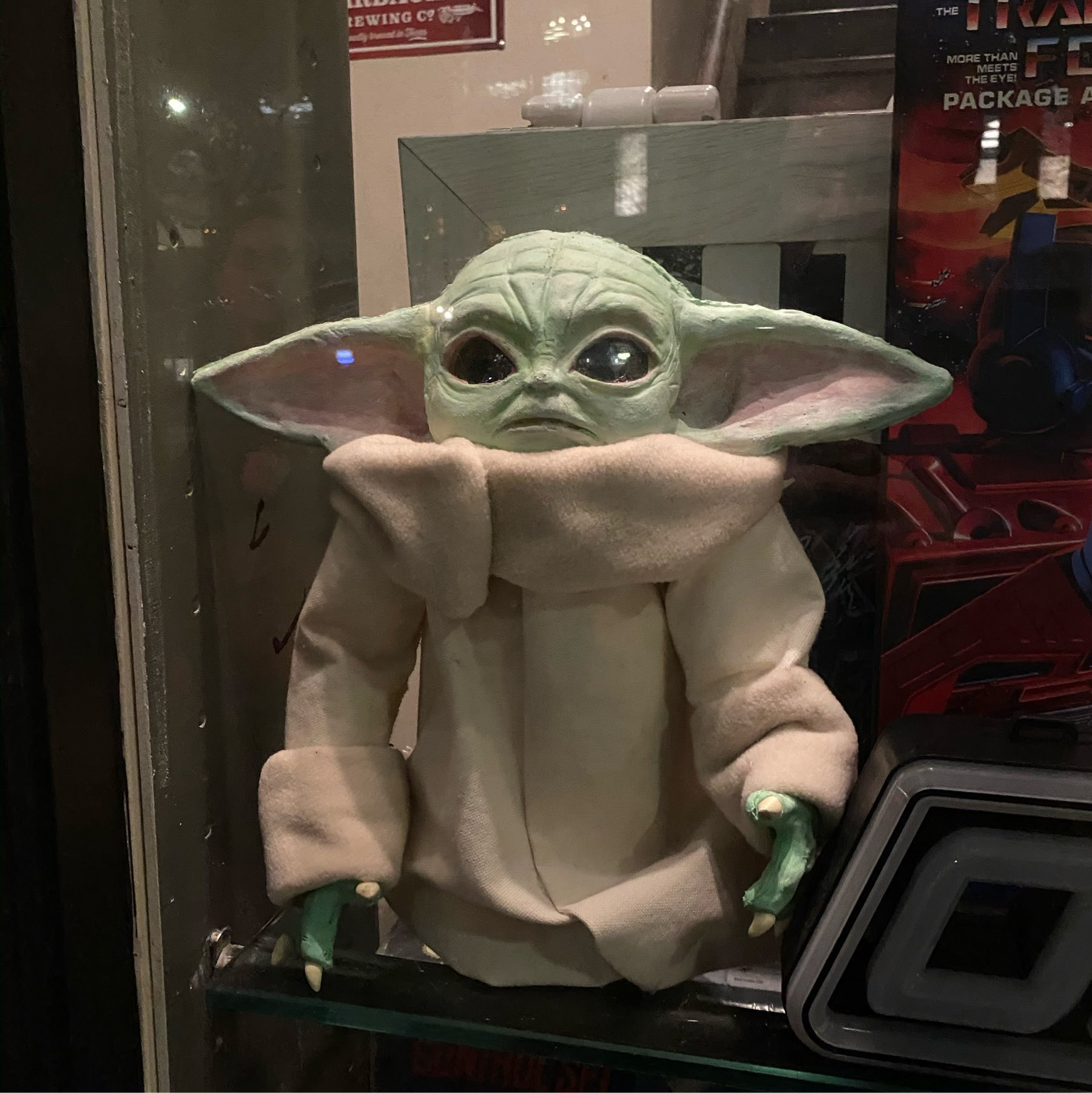 A Yoda doll in a window display.