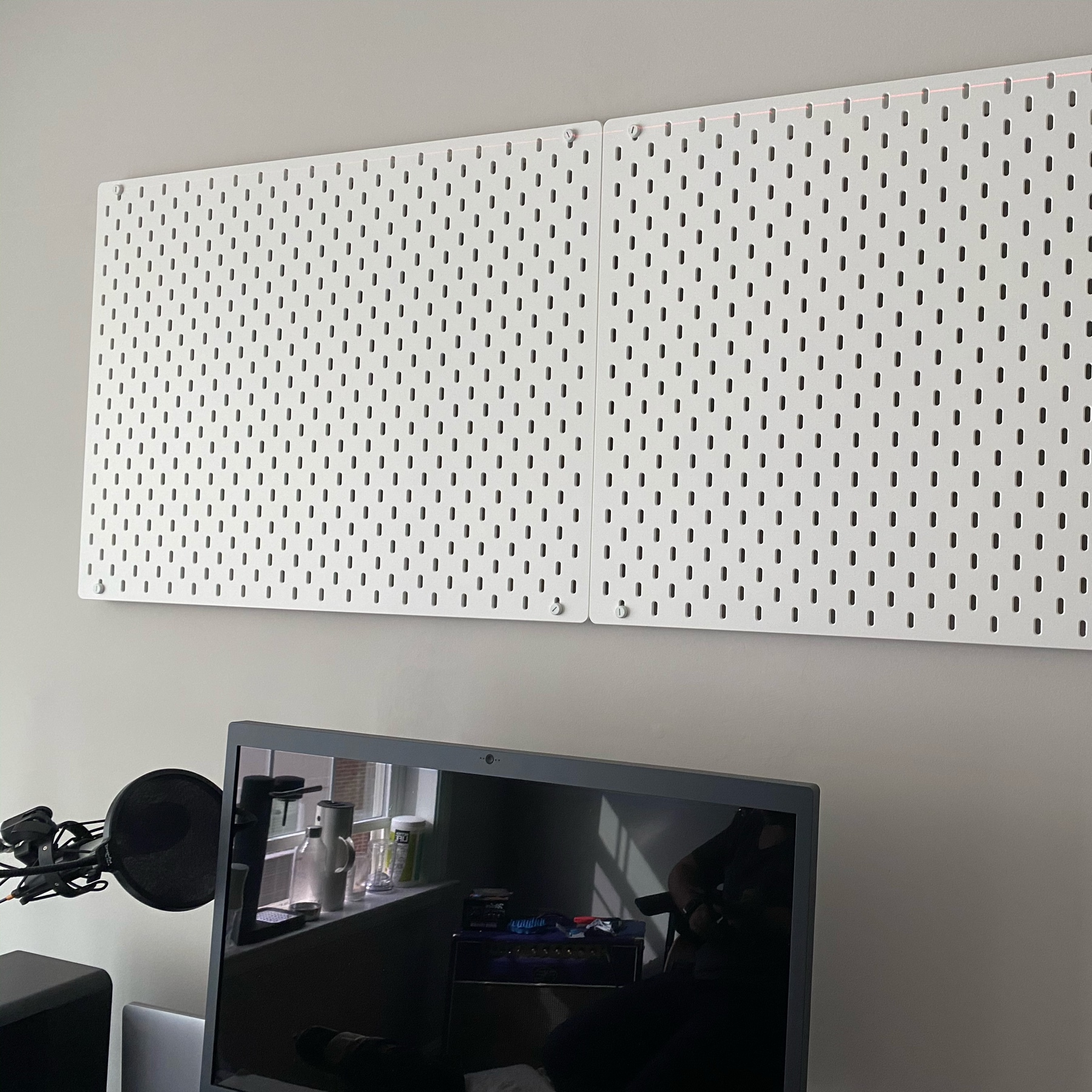 Two white IKEA Skadis pegboards mounted above my desk.