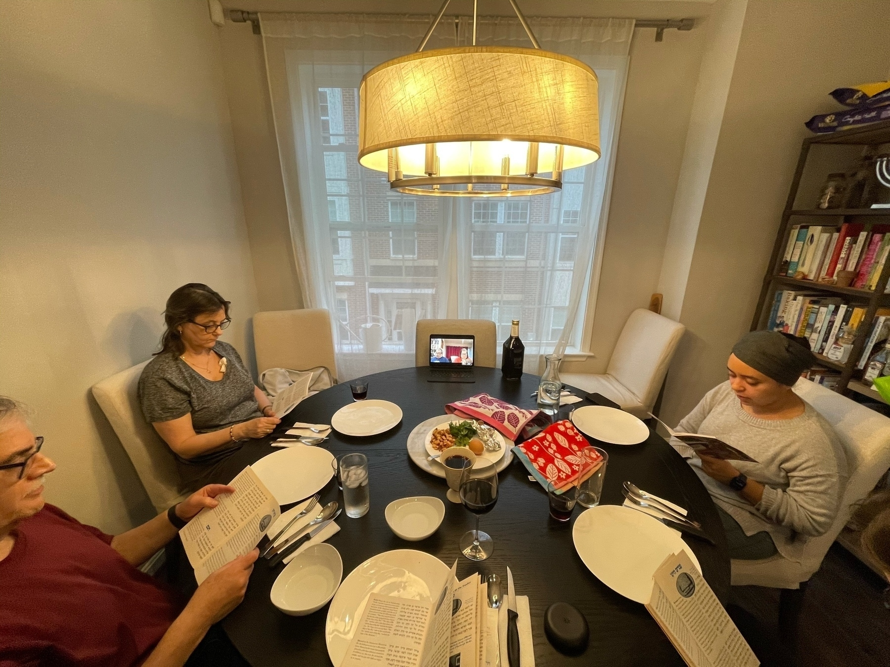 Family members around a table with one lonely iPad broadcasting those who could not safely celebrate in person.
