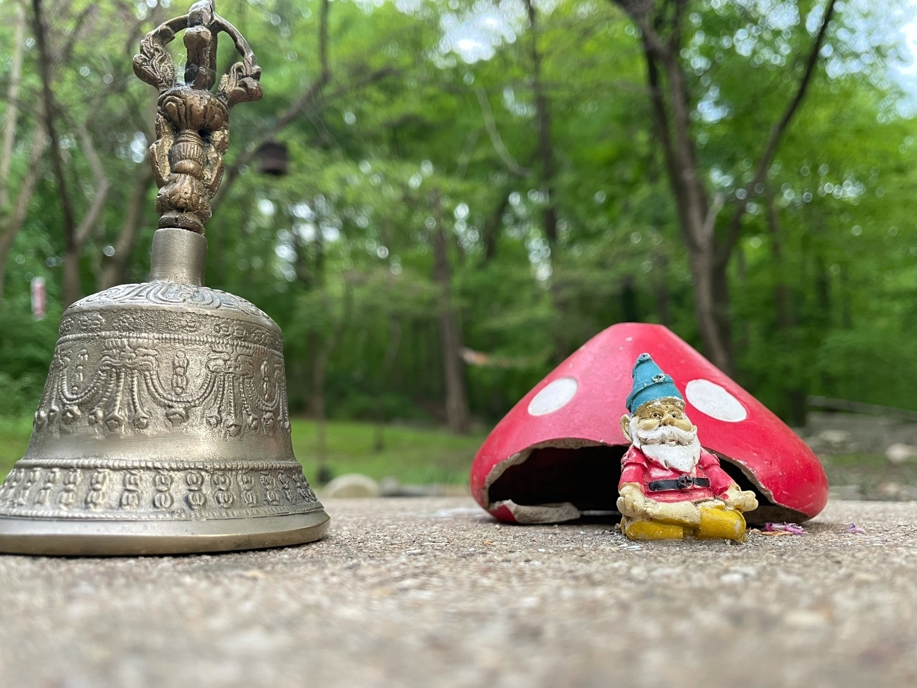 A bell and ceramic mushroom, the mushroom covering a small gnome.