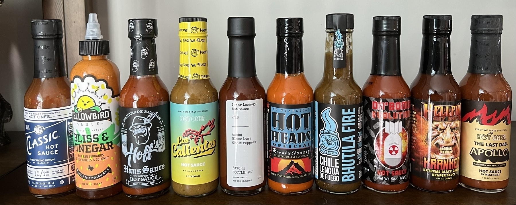Ten hot sauces from Hot Ones lined up side-by-side.