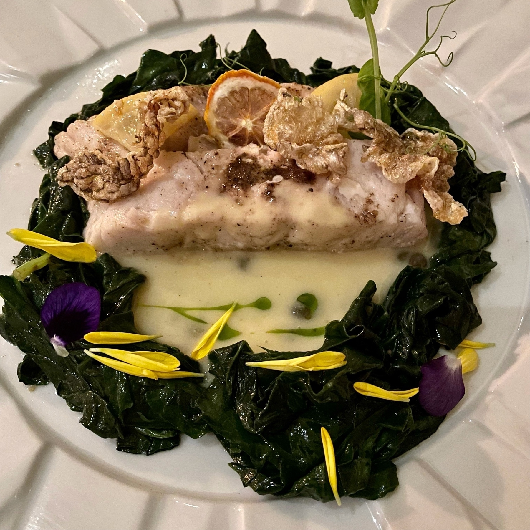 Sea bass surrounded by sautéed spinach in a beurre blanc.