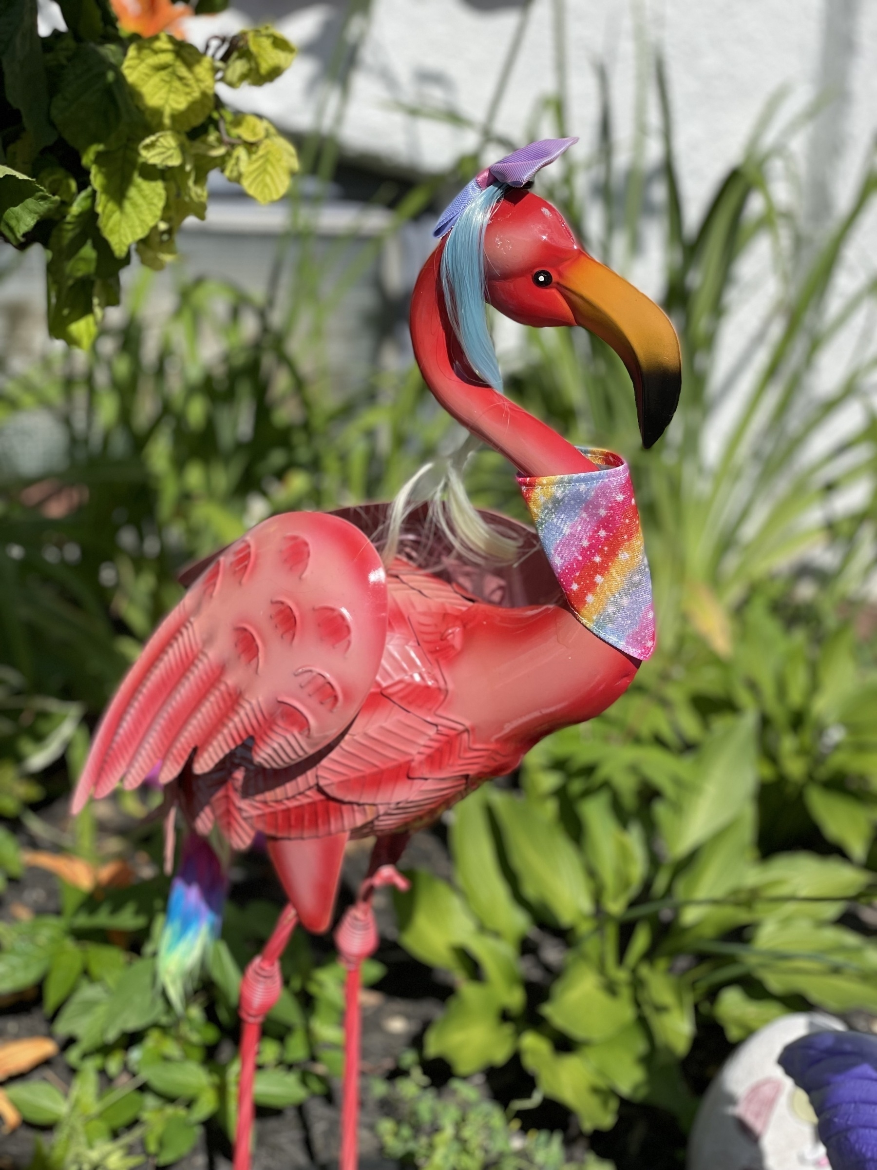 A plastic pink flamingo with bright blue wig.