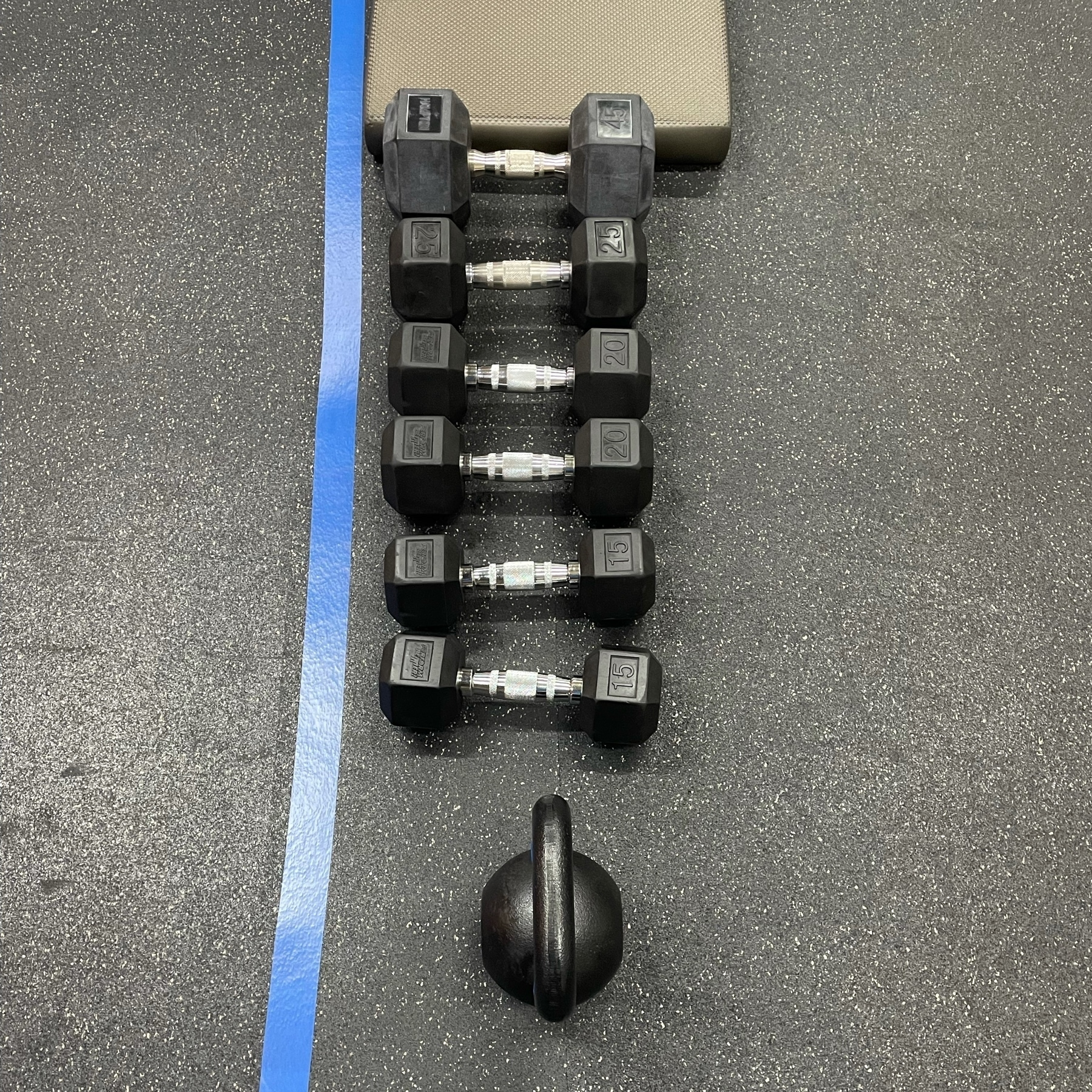 A collection of weights lined up on the floor at my gym.