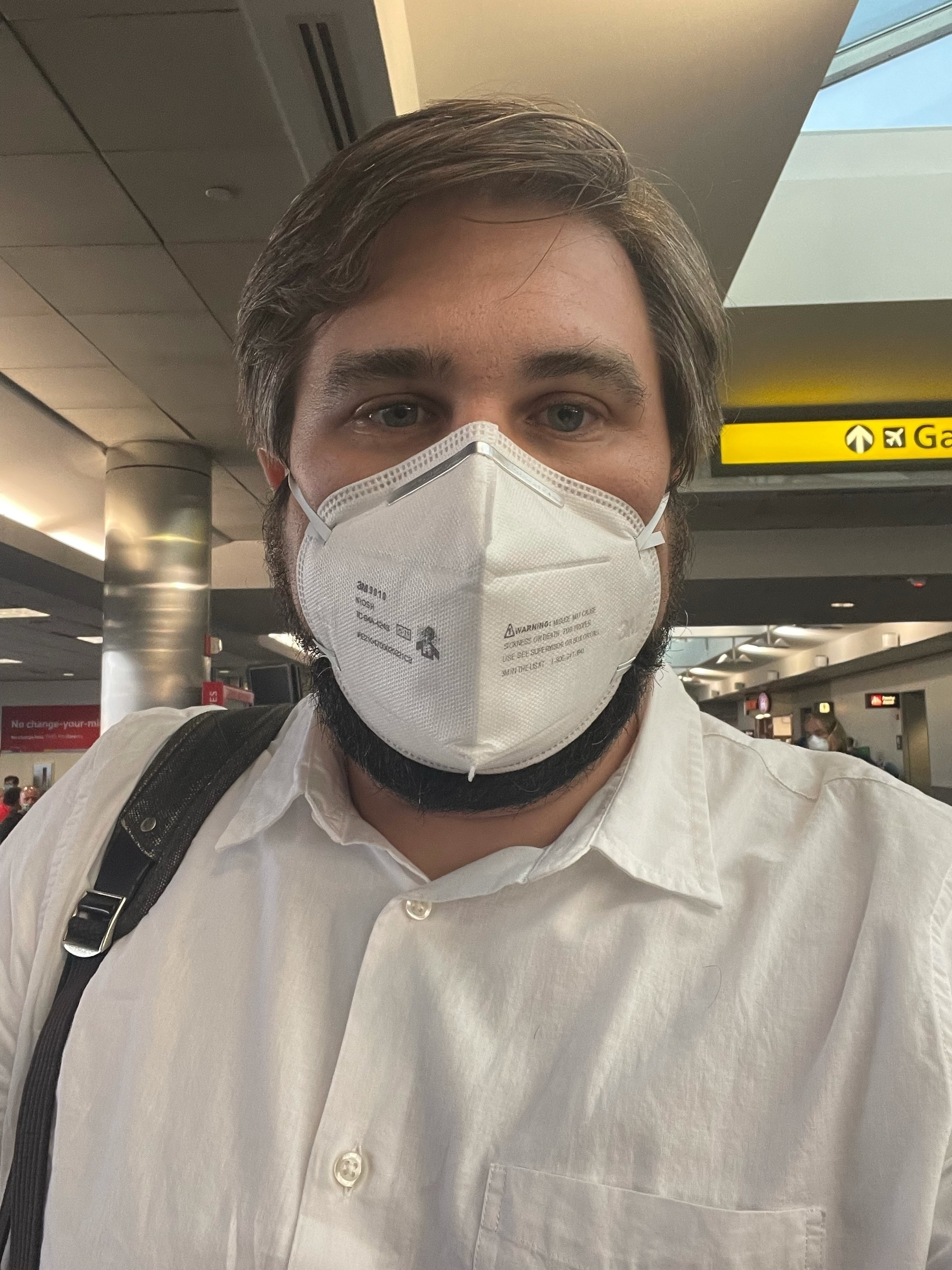 Selfie with an N95 mask and white shirt on at BWI.