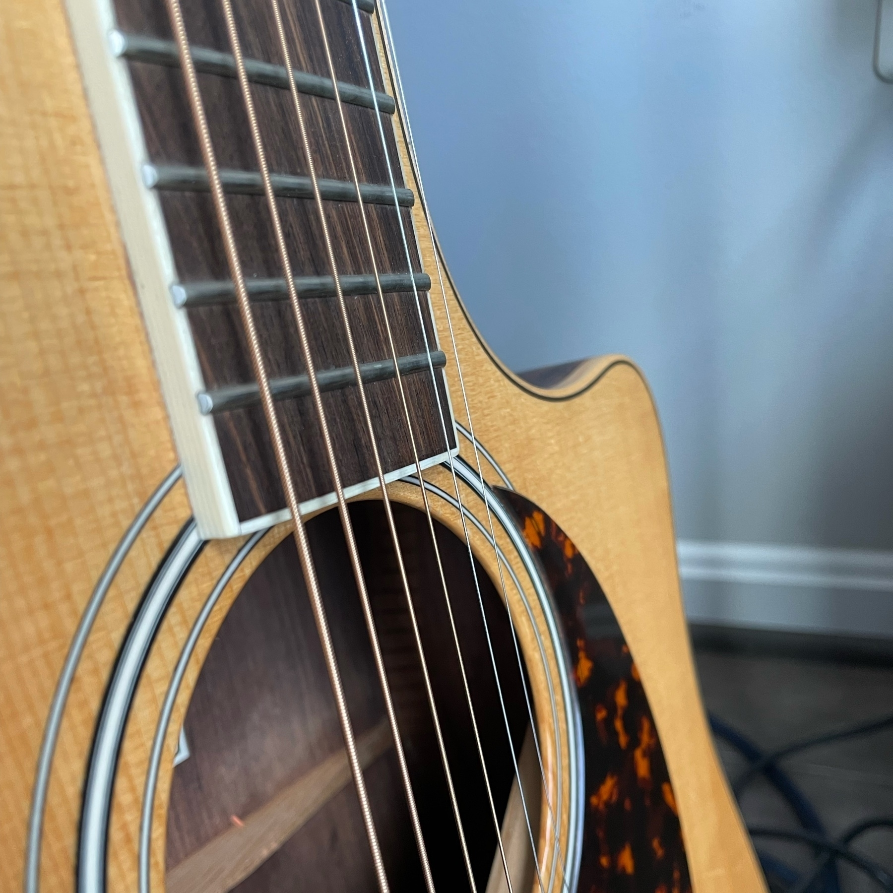 Close up of my acoustic guitar, where the neck meets the body, with a new set of strings.