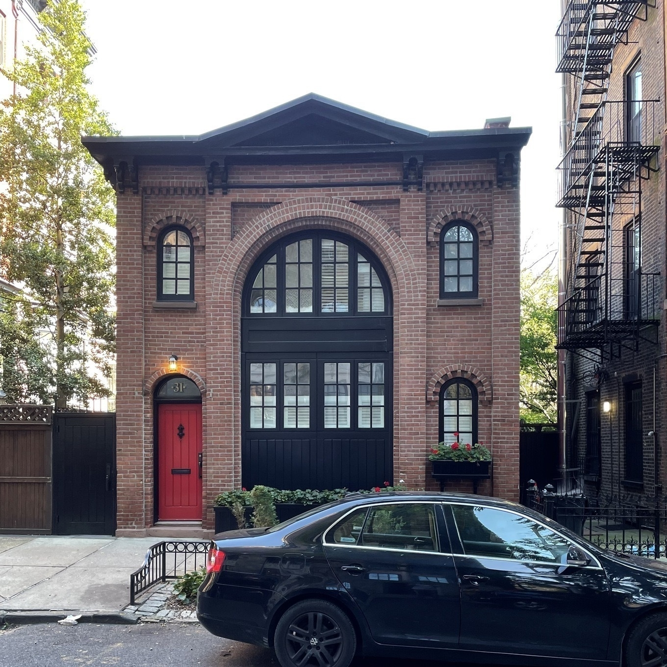 Brick house with a red door and two levels of black windows in an archway