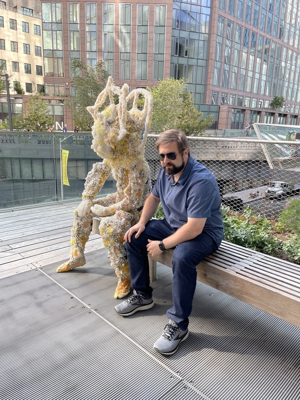 Me posing next to a statue on a bench at Atlantic Yards