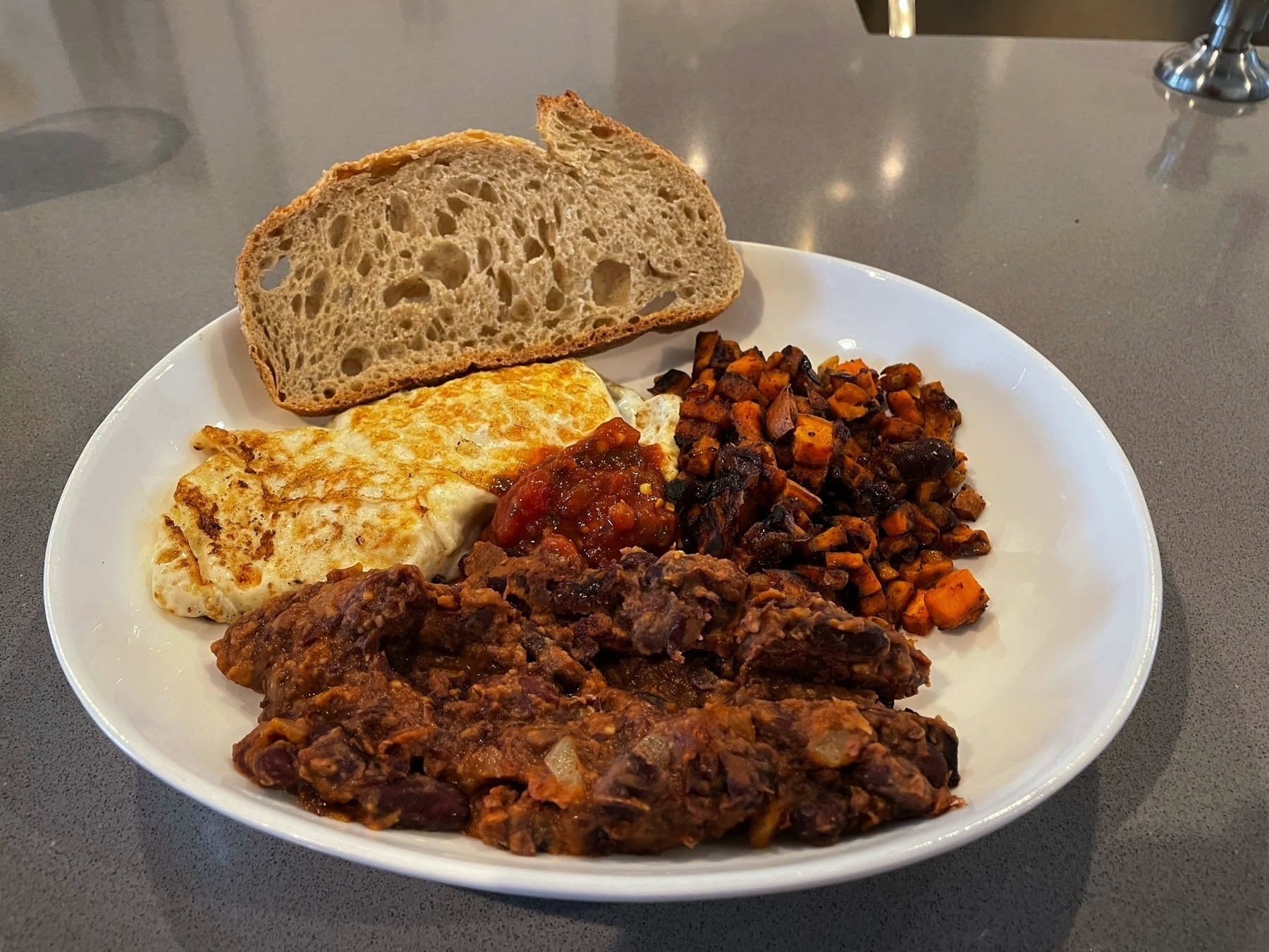 Breakfast plate with two eggs, sweet potato hash, beans, and a slice of sourdough.