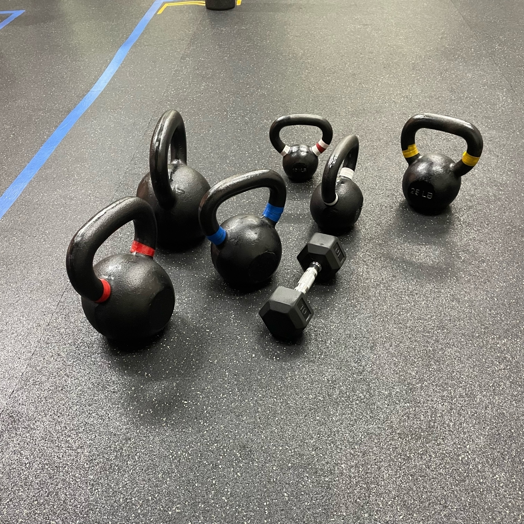 A collection of 6 kettlebells and a dumbell on the gym mat.