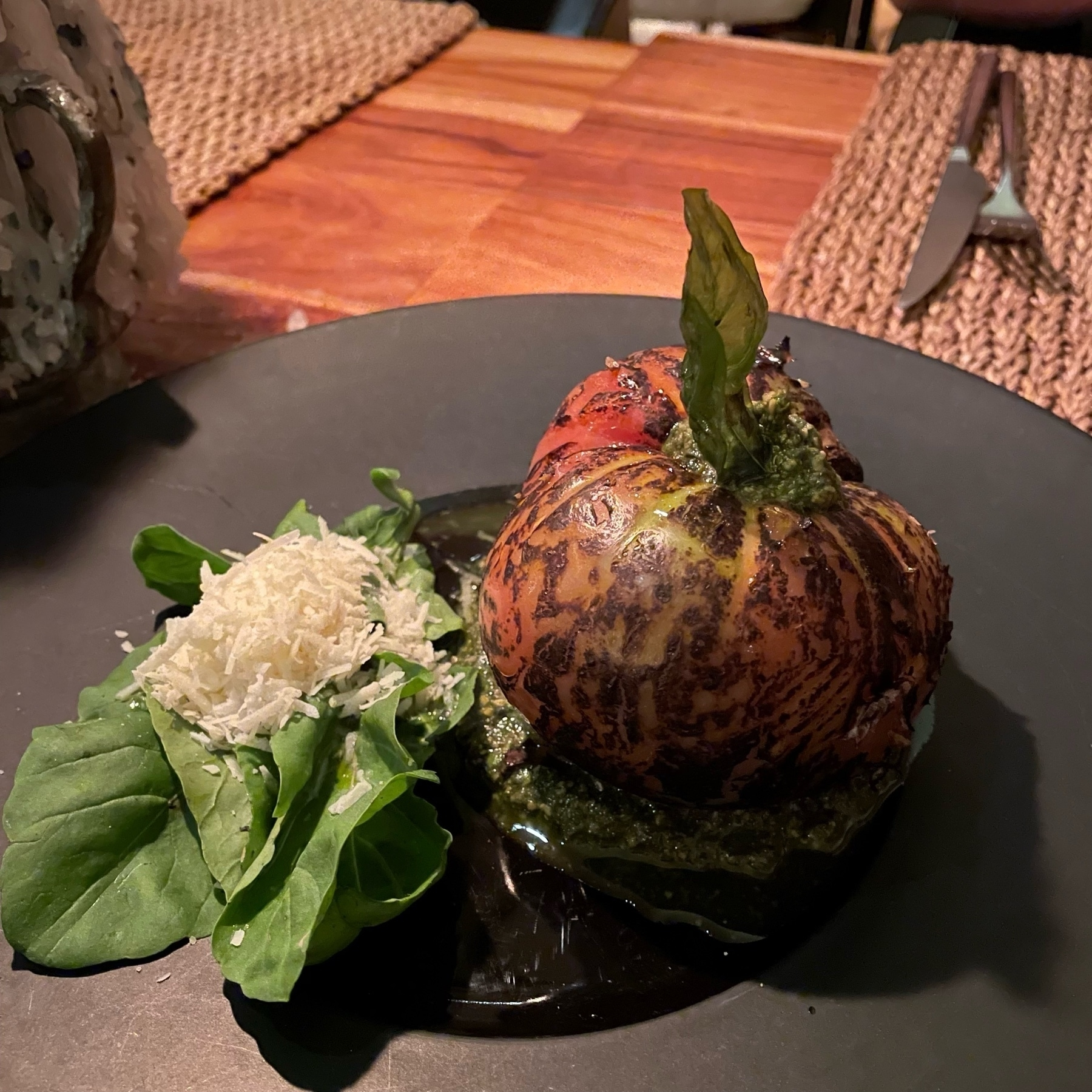 A large heirloom tomato beside a stack of basil leaves with some parm