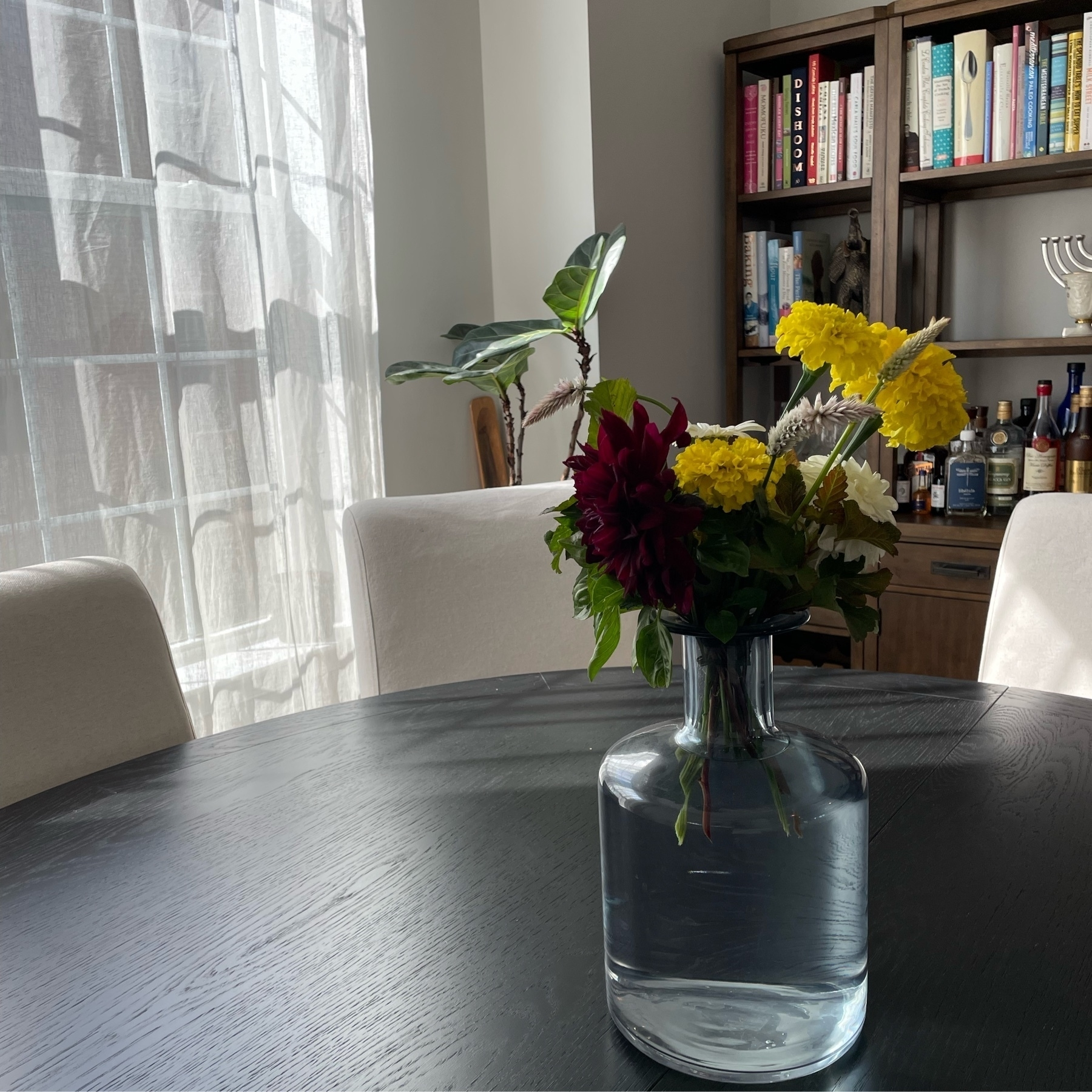 Flowers in a light blue vase on a black table with a window and bar in the background.