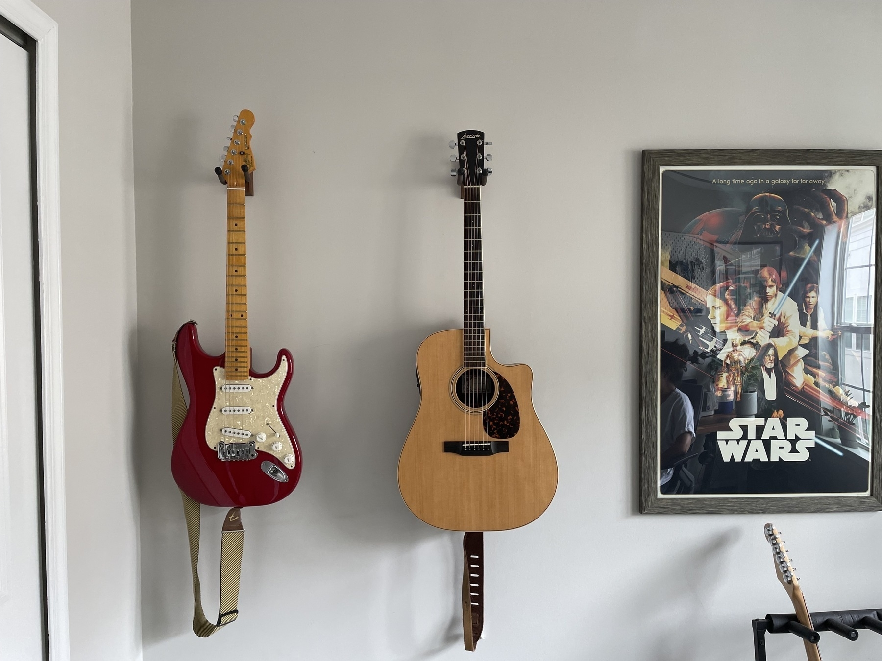 Electric guitar and acoustic guitar, wall mounted.