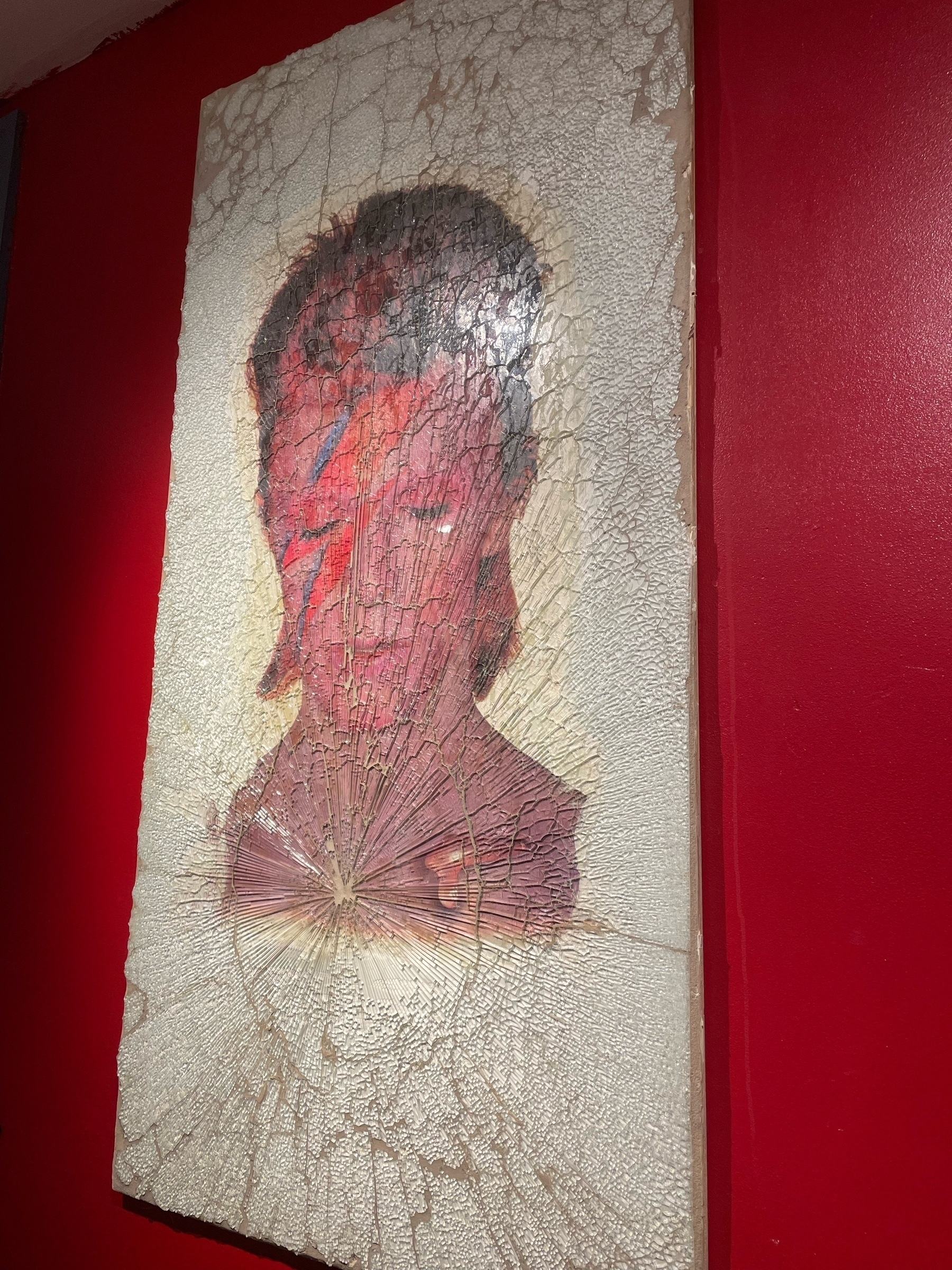 David Bowie as Ziggy Stardust behind shattered glass on a red wall.