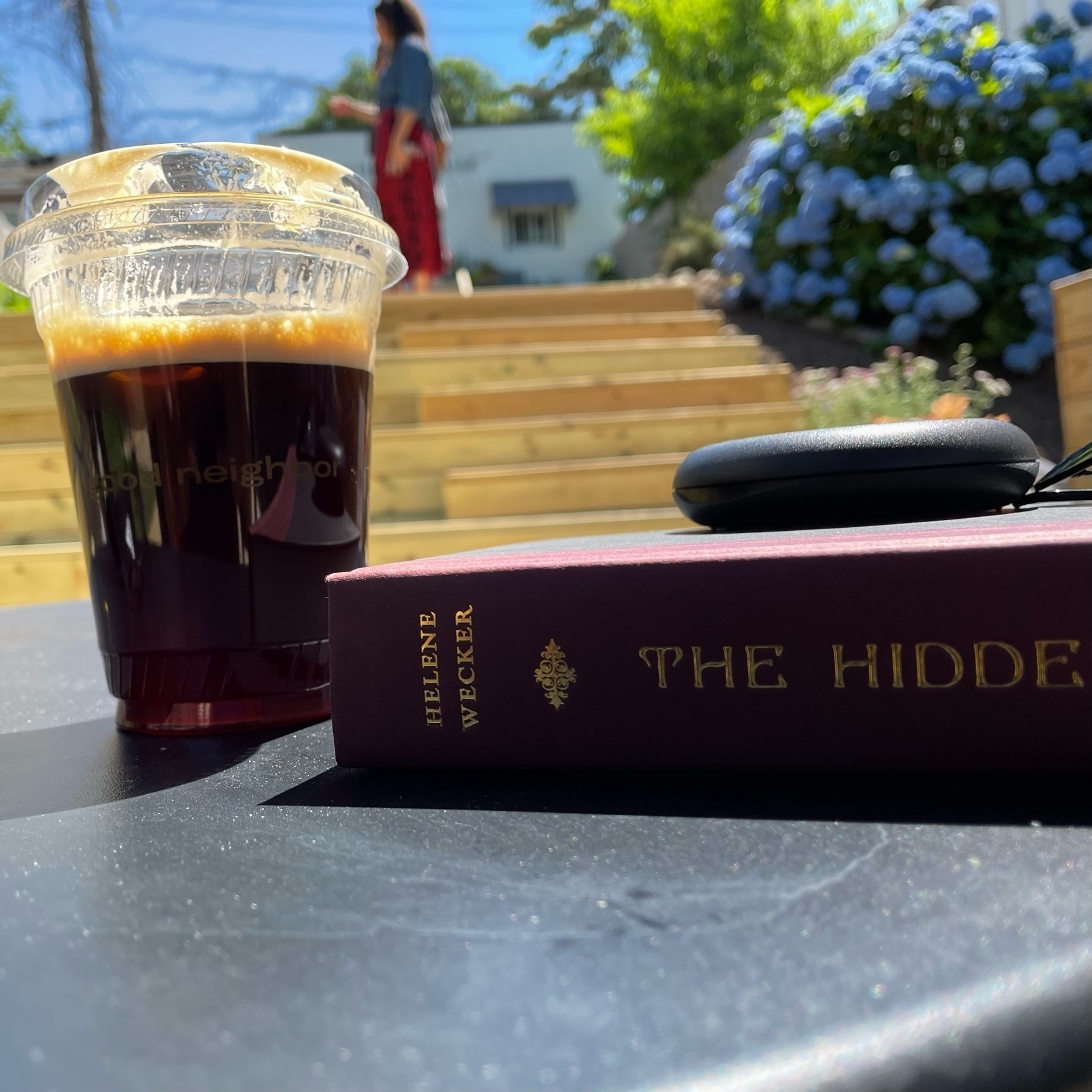 Iced coffee with The Hidden Palace hardcover on a table outside at Good Neighbors