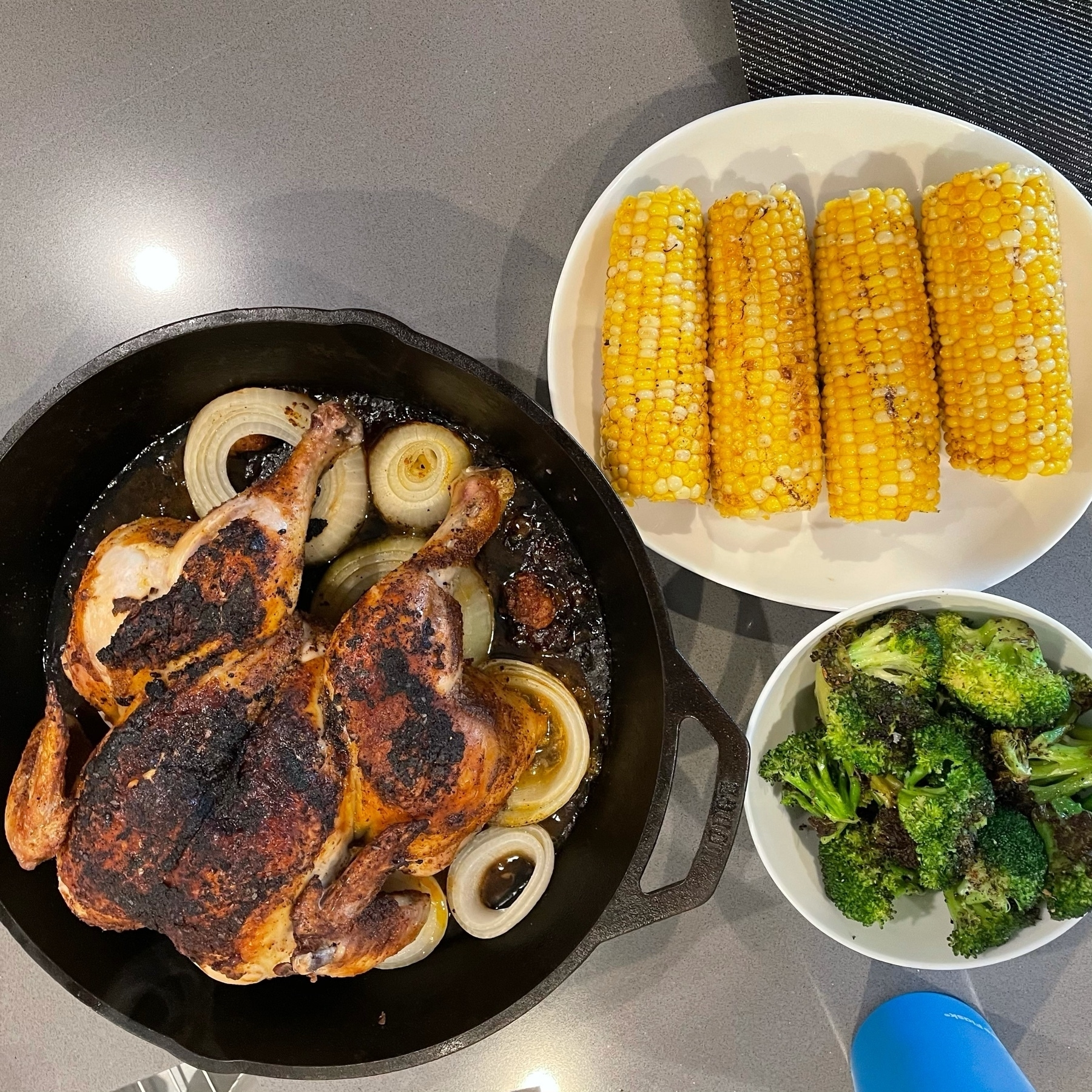 A whole chicken in a cast iron, corn on the cob, and broccoli.